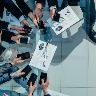 Z góry widok. zespół biznesowy używa smartfonów do pracy z danymi finansowymi.