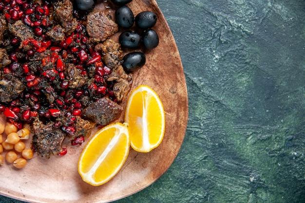 Z góry zamknij widok pyszne plastry mięsa smażone z fasolą, winogronami i plasterkami cytryny wewnątrz płyty na ciemnym tle