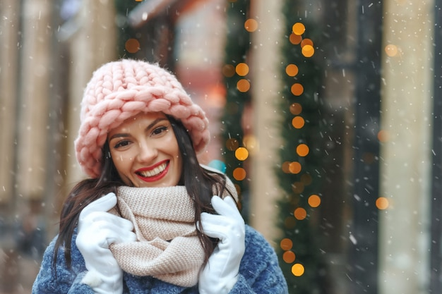 Z klasą brunetka kobieta w płaszczu spaceru po mieście w śnieżną pogodę. pusta przestrzeń