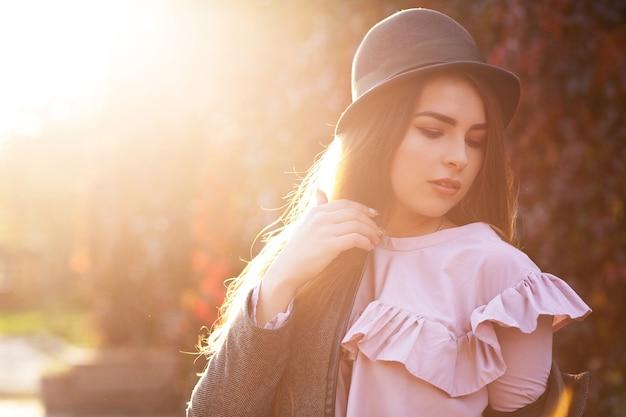Z klasą brunetka opalona kobieta z naturalnym makijażem na sobie kapelusz i płaszcz. miejsce na tekst