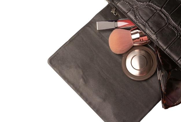 Z kobiecej torebki wypadają pędzel kabuki, puder i szminka. białe tło