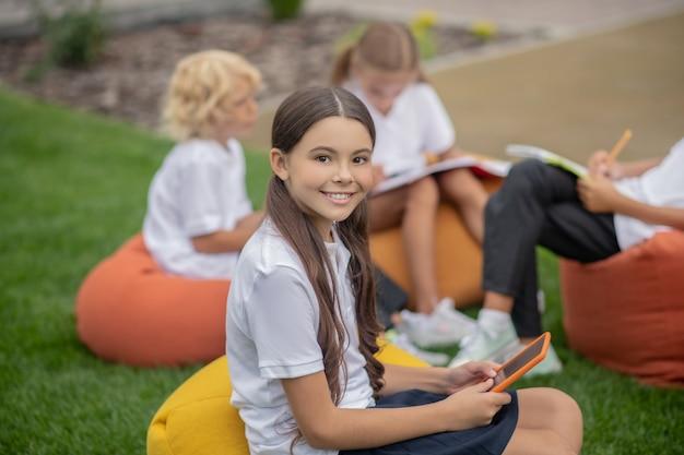 Z kolegami z klasy. śliczna ciemnowłosa dziewczyna siedzi z kolegami z klasy i uśmiecha się