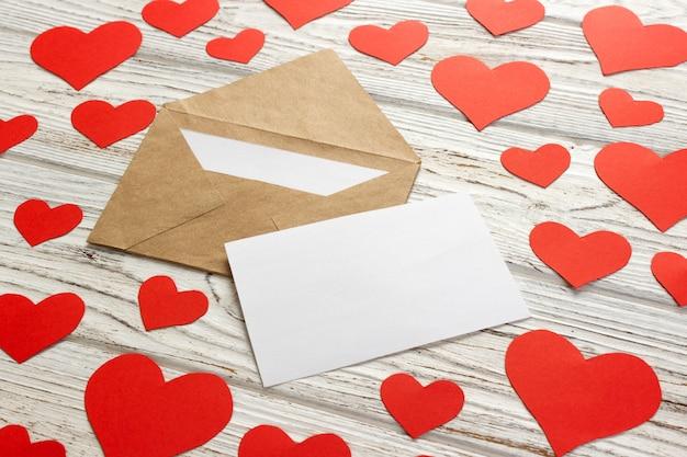 Z koperty wylatują serca. list miłosny. tło walentynki na drewnianym tle