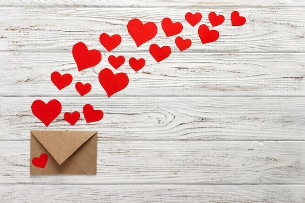 Z koperty wylatują serca. list miłosny. tło walentynki