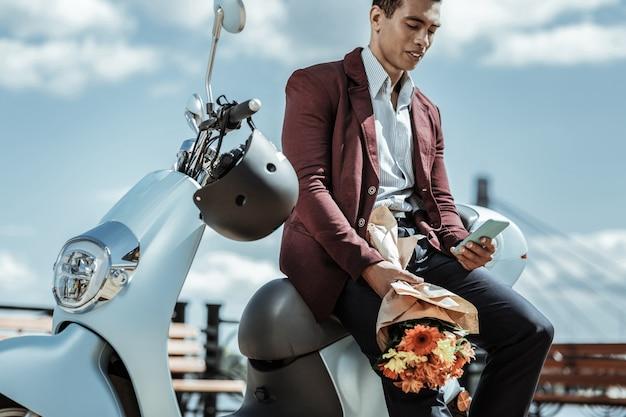 Z kwiatami. niski kąt pewnego siebie, sympatycznego faceta niosącego bukiet kwiatów i opartego na motocyklu