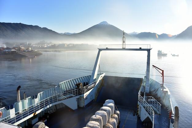 Z łodzi mglisty widok na jezioro i góry