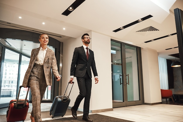 Z lotniska do hotelu. para w podróży służbowej wchodzi w drzwi hotelu. mężczyzna i kobieta idą z bagażem