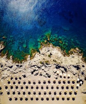 Z lotu ptaka widać parasole, piasek i egzotyczne morze.