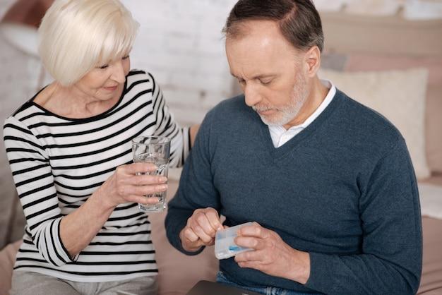 Z miłością. starszy mężczyzna wyjmuje tabletki ze skrzynki, podczas gdy jego żona trzyma dla niego szklankę wody.