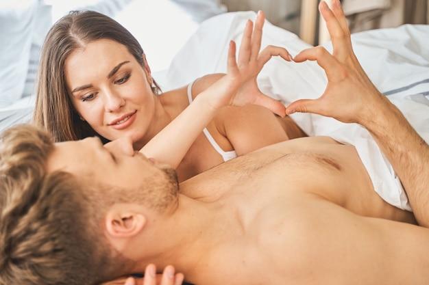 Z miłością. wesoli młodzi ludzie leżą w swoim łóżku i robią palcami kształt serca heart