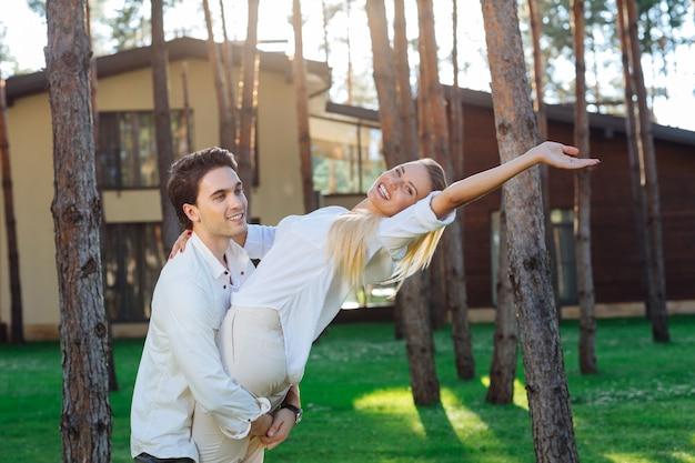 Z moim mężem. miła zachwycona kobieta uśmiechnięta, czując się bezpieczna i chroniona ze swoim mężem