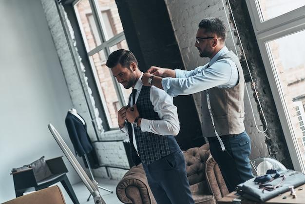 Z myślą o każdym szczególe. młody modny projektant pomagający swojemu klientowi się ubrać