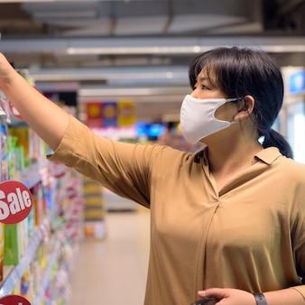 Z nadwagą azjatycka kobieta z maską chroniącą przed epidemią wirusa korony, która robi zakupy w supermarkecie