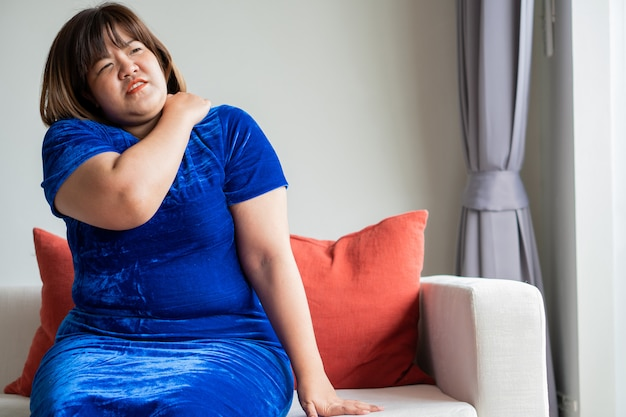 Z nadwagą azjatyckie kobiety siedzą na kanapie w salonie.
