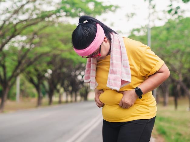 Z nadwagą kobieta trzyma jej brzucha. koncepcja odchudzania