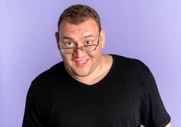 Z nadwagą mężczyzna w okularach na sobie czarną koszulkę zaskoczony i szczęśliwy na niebiesko