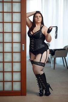 Z nadwagą perwersyjna kobieta w erotycznej bieliźnie trzyma skórzany bicz.