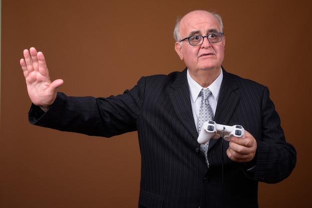 Z nadwagą starszy biznesmen grając w gry i trzymając kontroler do gier