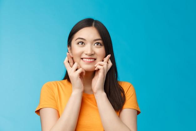 Z nadzieją podekscytowana urocza optymistyczna azjatka wierzy, że marzenia się spełniają, trzymaj kciuki na szczęście, patrz w górę uśmiechając się, modląc się, pragnąc wygrać, osiągnąć sukces, uczeń mający nadzieję na otrzymanie stypendium.