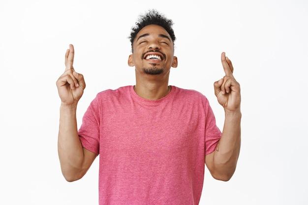 Z nadzieją uśmiechnięty afroamerykański męski model, zamknięte oczy, uśmiechnięty z ulgą, krzyżujące palce powodzenia, życzenie, modlenie się lub oczekiwanie na coś, stojąc w różowej koszulce na białym