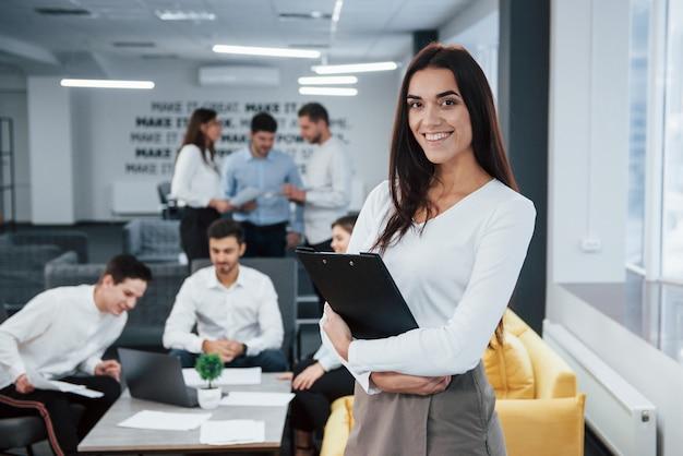 Z notatnikiem w rękach. portret młoda dziewczyna stojaki w biurze z pracownikami przy tłem