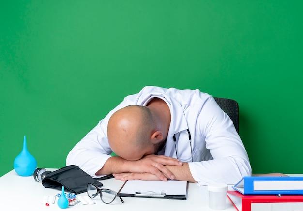 Z obniżoną głową młody lekarz płci męskiej ubrany w szlafrok i stetoskop siedzi przy biurku z narzędziami medycznymi na białym tle na zielonej ścianie