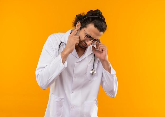 Z obniżoną głową młody lekarz z okularami medycznymi na sobie szlafrok medyczny ze stetoskopem zamknięte uszy na izolowanej żółtej ścianie z miejscem na kopię