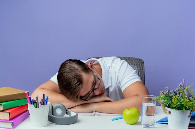 Z obniżoną głową młody przystojny student płci męskiej siedzi przy biurku z narzędziami szkolnymi w okularach