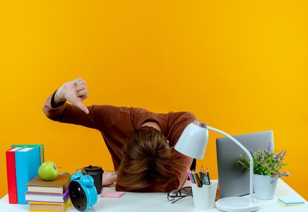 Z obniżoną głową młody uczeń chłopiec siedzi przy biurku z narzędziami szkolnymi kciuk w dół na białym tle na żółtej ścianie
