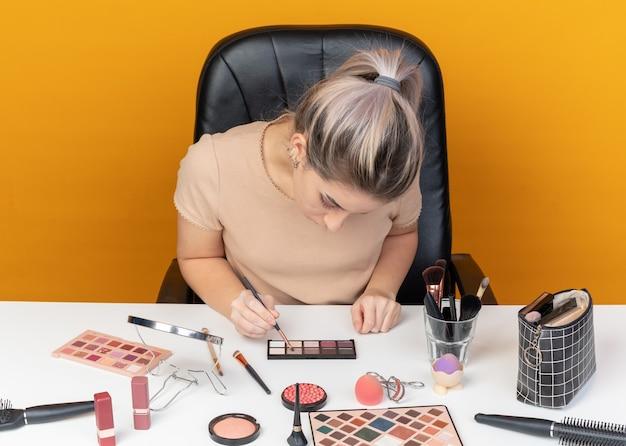 Z opuszczoną głową młoda piękna dziewczyna siedzi przy stole z narzędziami do makijażu, stosując cień do powiek z pędzlem do makijażu na białym tle na pomarańczowym tle