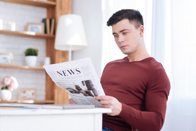 Z ostatniej chwili. przystojny, ambitny mężczyzna wolny strzelec trzymając gazetę podczas badania artykułu