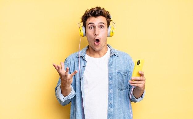 Z otwartymi ustami i zdumieniem, zszokowany i zdumiony niewiarygodną niespodzianką. koncepcja słuchawek i smartfona