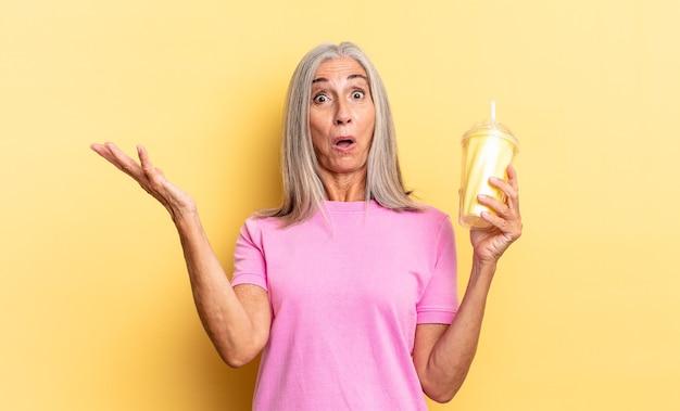 Z otwartymi ustami i zdumiony, zszokowany i zdumiony niesamowitą niespodzianką i trzymając koktajl mleczny
