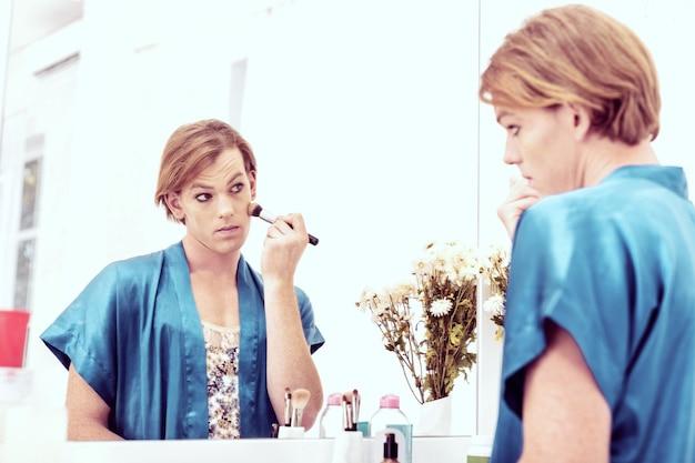 Z pędzelkiem do makijażu. przyjemna podejrzana transseksualistka maskująca męskie rysy twarzy produktami kosmetycznymi