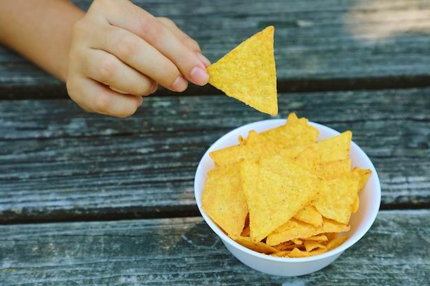 Z pełnej miski wyjmij ręcznie chips tortilla.