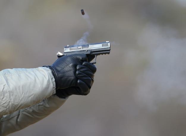 Z pistoletu strzelającego dwiema rękami, łuski wydobywające się z migawki i niebieski dym.