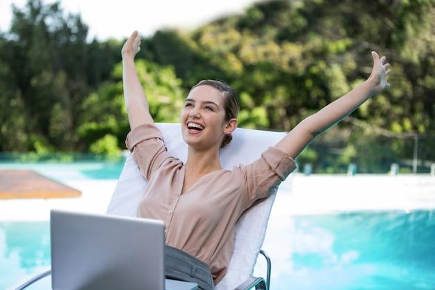 Z podnieceniem bizneswoman z laptopem blisko basenu