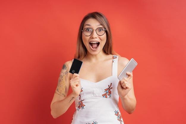 Z podnieceniem ładna młoda kobieta trzyma telefon i kartę kredytową w jej rękach