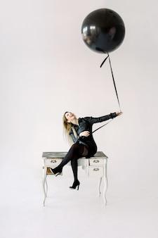 Z podnieceniem młoda dziewczyna w czerni sukni odświętności trzyma czerń balon i siedzi na białym rocznika stole odizolowywającym na białym tle. międzynarodowy dzień kobiet, szczęśliwego nowego roku, koncepcja przyjęcia urodzinowego