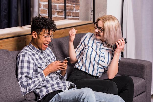 Z podnieceniem młoda kobieta patrzeje jej chłopaka używać telefon komórkowego