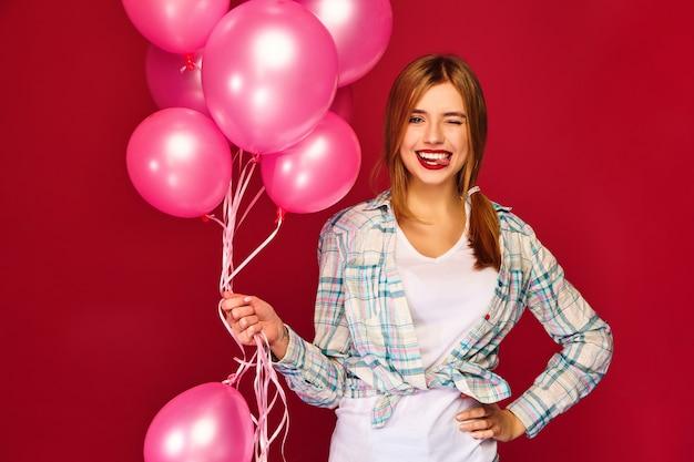 Z podnieceniem młoda kobieta pozuje z różowymi lotniczymi balonami