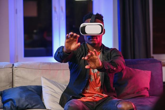 Z podnieceniem młody afroamerykański mężczyzna przedłuża rękę naprzód, używa rzeczywistości wirtualnej słuchawki obsiadanie na łóżku, kopii przestrzeń