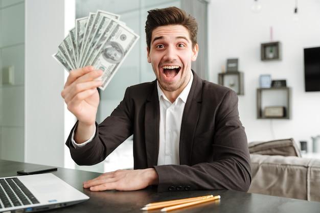 Z podnieceniem młody biznesmen pokazuje pieniądze używać laptop.
