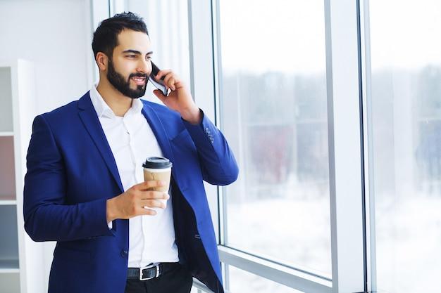 Z podnieceniem młody caucasian biznesmen świętuje zwycięstwo rozochoconego w nowożytnym biurze