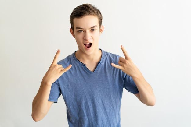 Z podnieceniem młody człowiek pokazuje róg znaki i krzyczy przy kamerą