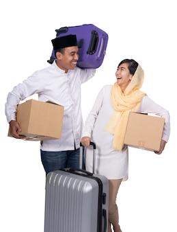 Z podnieceniem muzułmańska para z walizką na białym tle