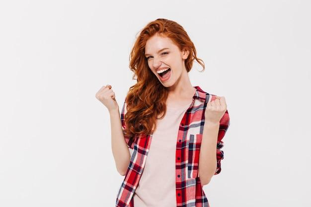 Z podnieceniem piękna młoda rudzielec dama pokazuje zwycięzcy gest.