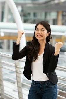 Z podnieceniem pomyślna biznesowa kobieta ono uśmiecha się i podnosić ręki up świętuje z szczęśliwie