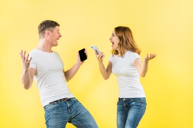 Z podnieceniem potomstwo pary mienia telefon komórkowy w ręce krzyczy z radością