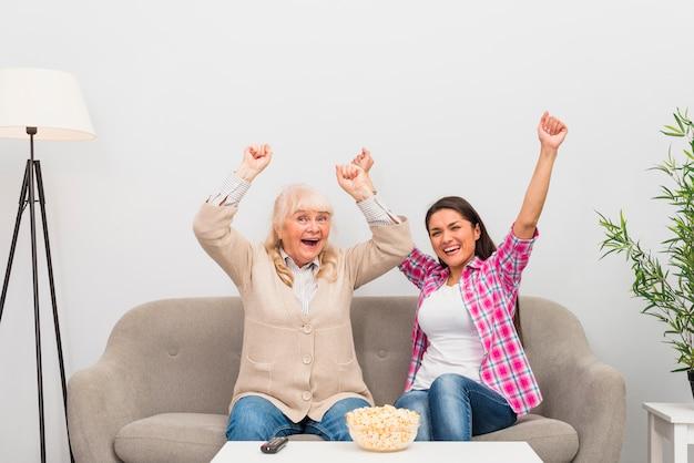 Z podnieceniem seniora matki i córki obsiadanie na kanapie podnosi ich ręki podczas gdy oglądający tv